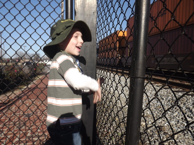Standing on the platform: Max gets a little excited as a Norfolk Southern freight train passes by the Bessemer Hall of History Museum, which is housed in an old train depot.